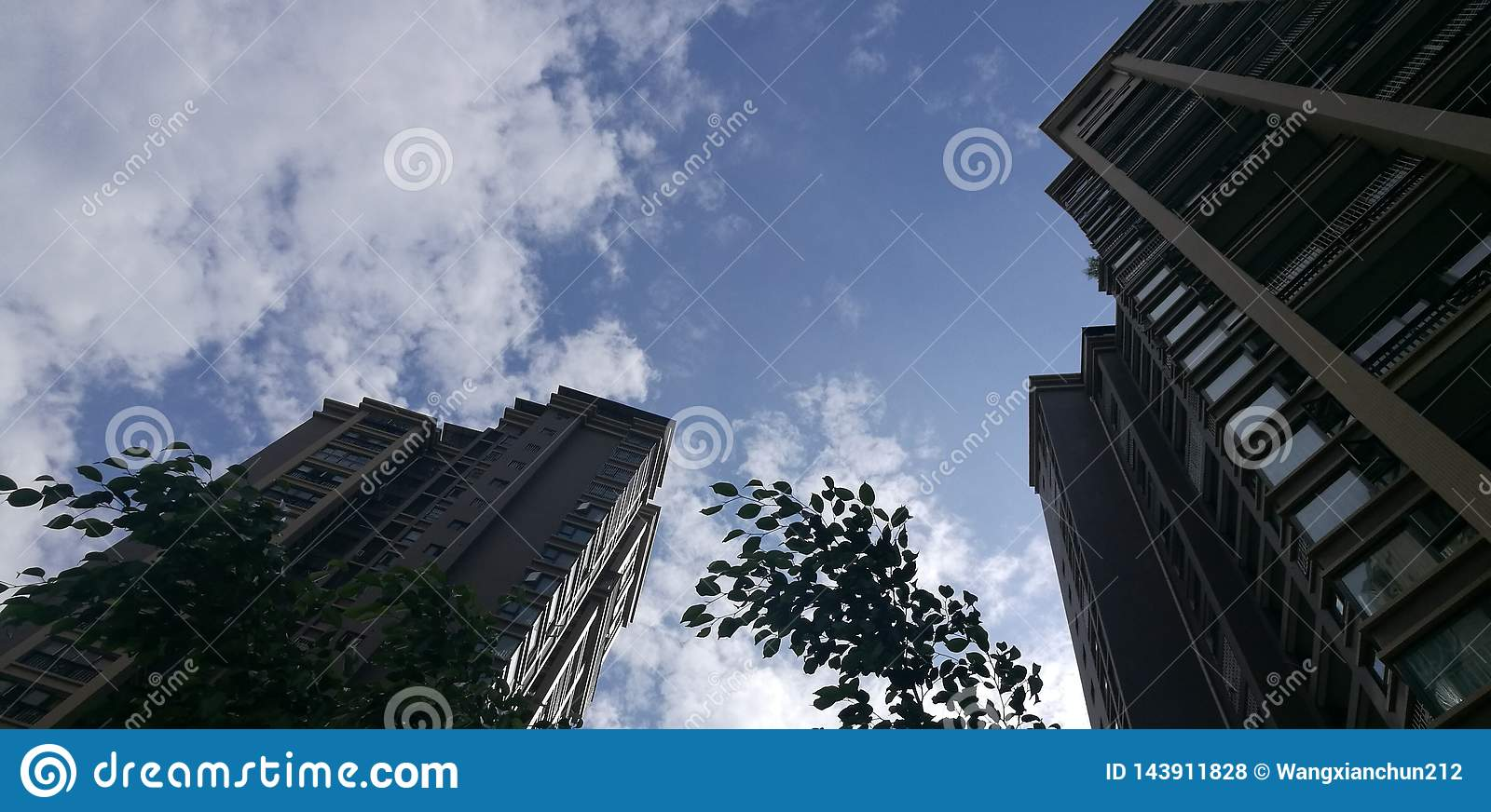 High-rise building under blue sky and white clouds