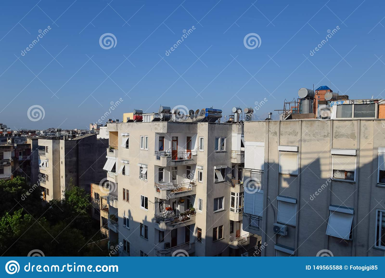 High-rise buildings in Antalya with barrels for water heating on the roof and sun blinds on the