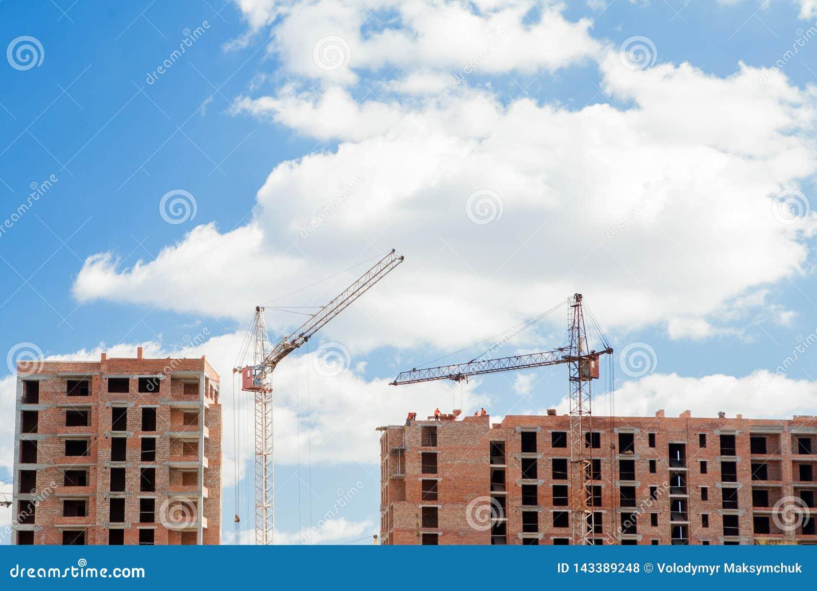 High-rise multi-storey buildings under construction. Tower cranes near building. Activity, architecture, development process,