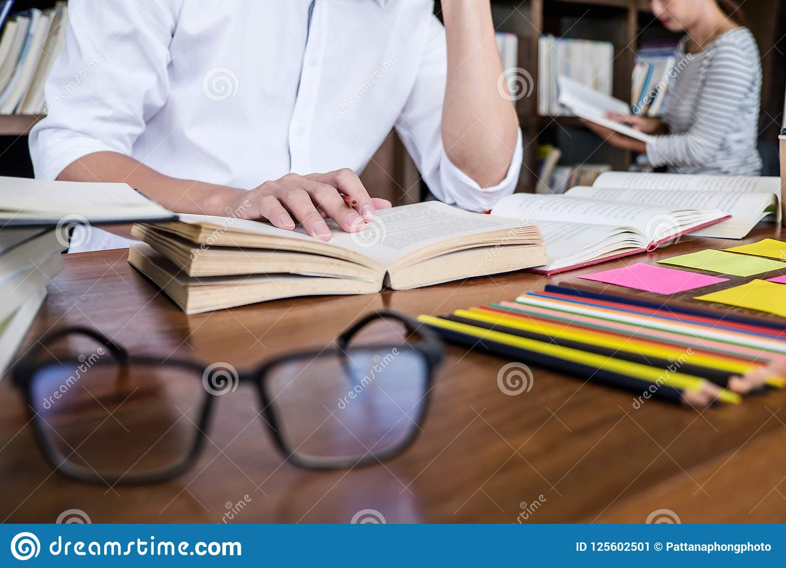 High School ou grupo de estudante universitário que senta-se na mesa na biblioteca
