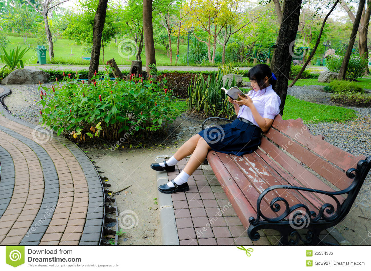 Thai high-schoolgirl reading in the park. She is relaxing.