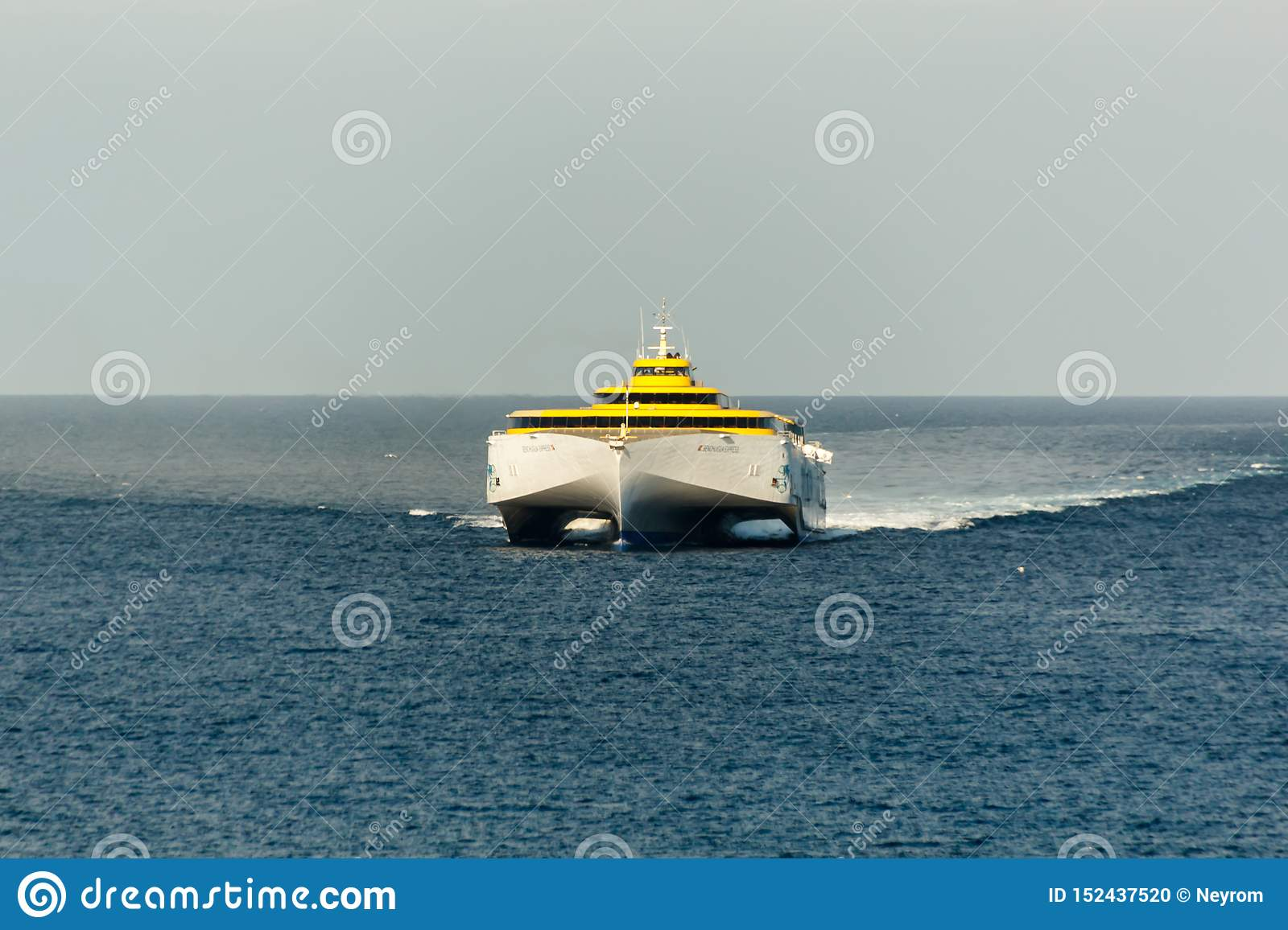 High-speed ferry going on a head-on course, shot from a long distance. Crossed waves and a smoky sky over the horizon line