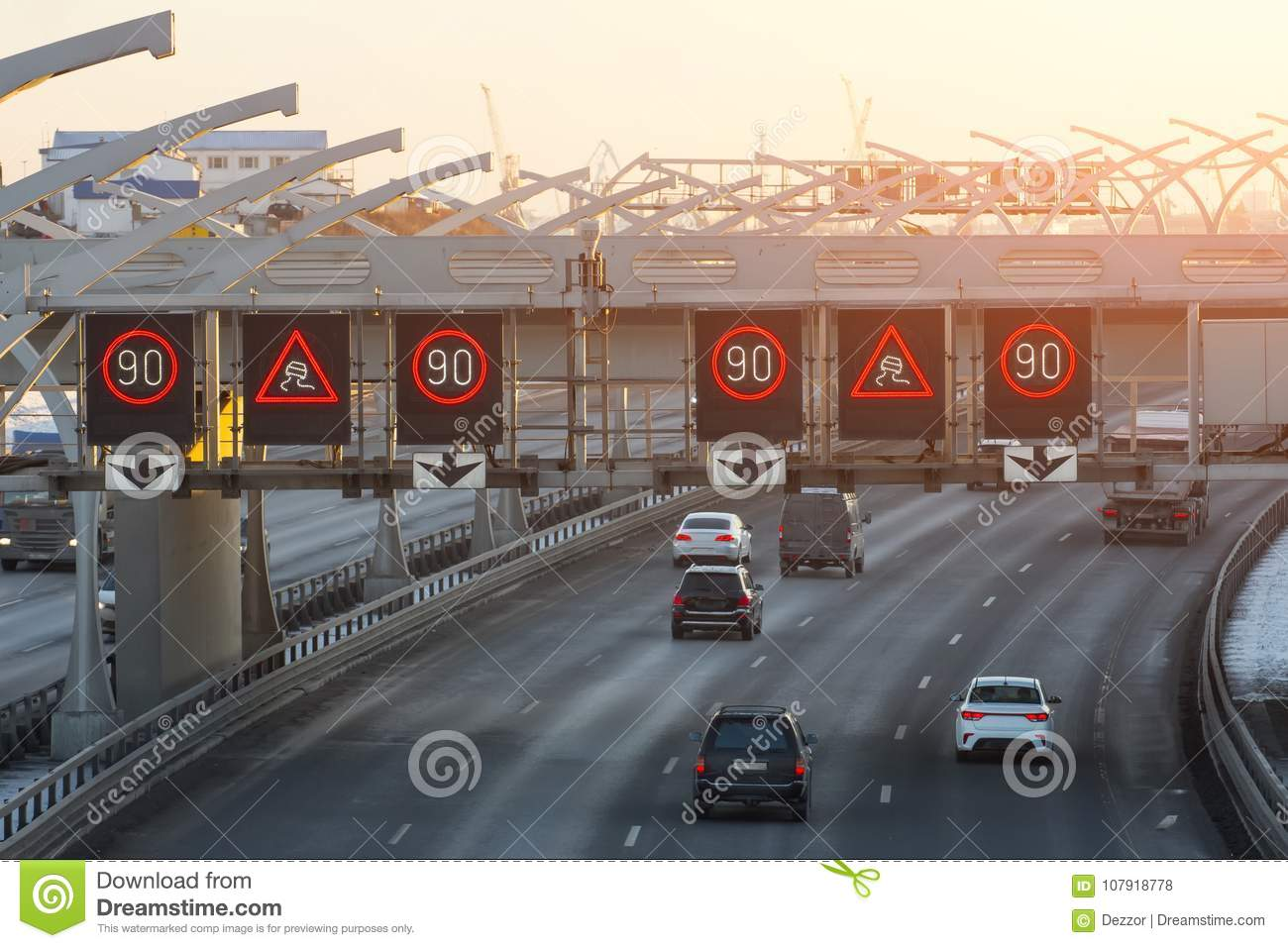 High-speed highway with traffic cars and speed limit signs and a slippery road warning.