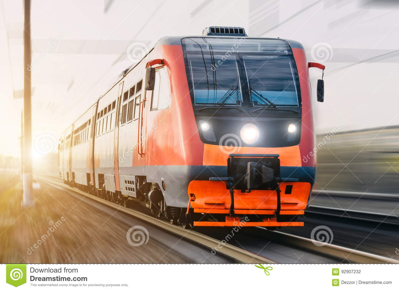 High-speed red passenger train rushing through the railway in the evening at sunset.