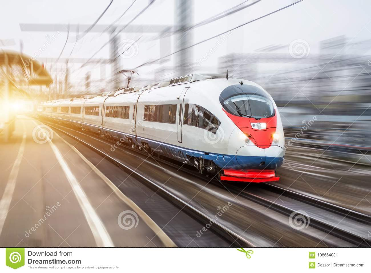 High speed train rides at high speed at the railway station in the city.