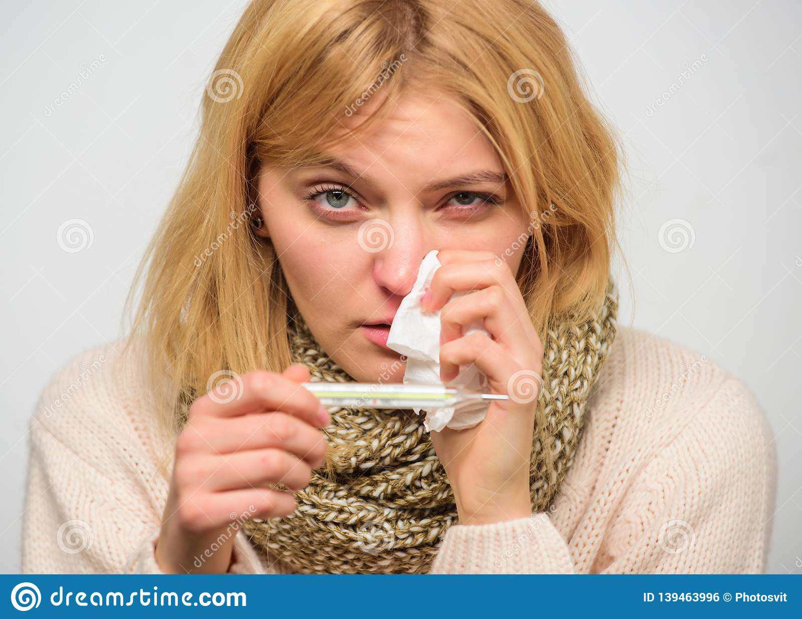 High temperature concept. Take temperature and assess symptoms. Measure temperature. Woman feels badly ill sneezing