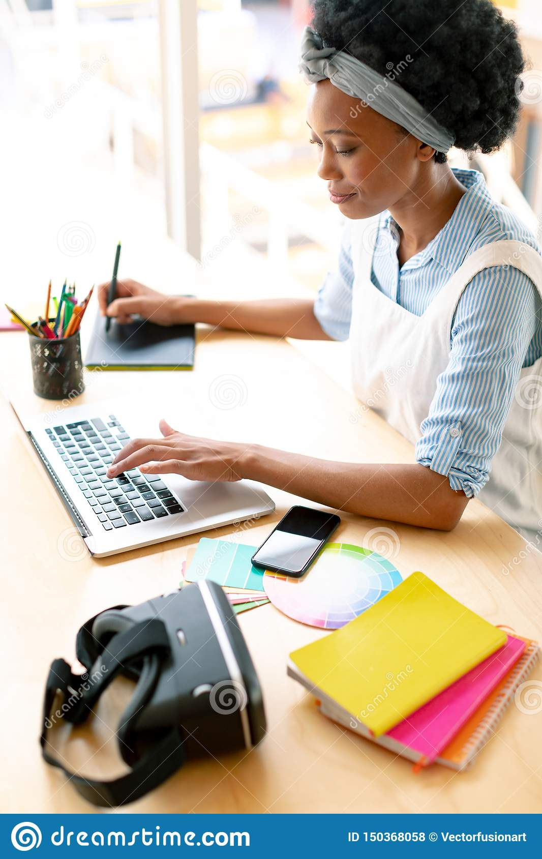 Female graphic designer using graphic tablet and laptop at desk