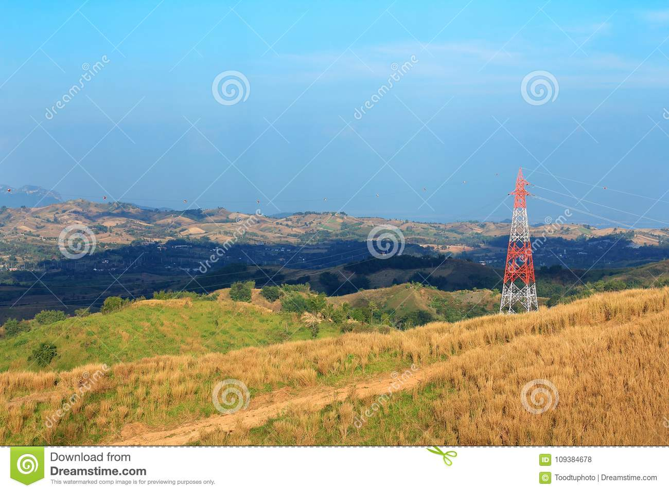 High-voltage tower on mountain with meadow,electrical poles and cables in rural areas