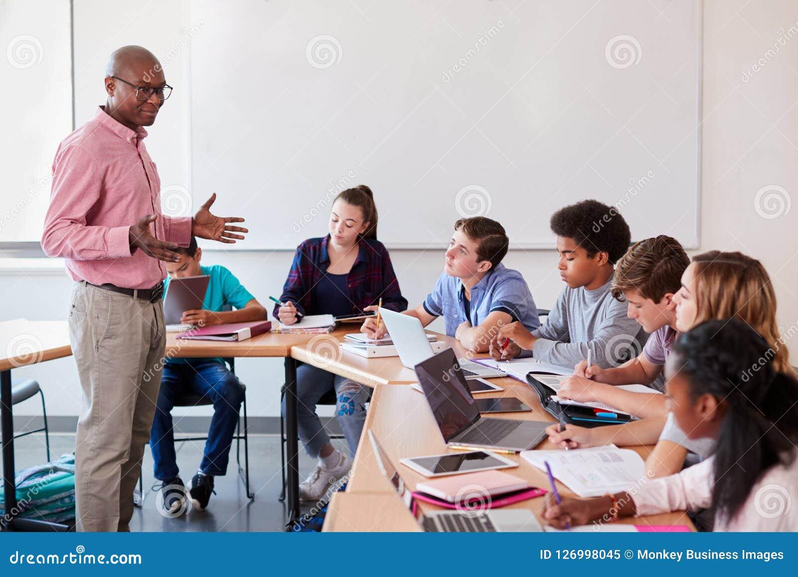 Highschoollehrer Talking To Pupils, das Digital-Geräte in der Technologie-Klasse verwendet