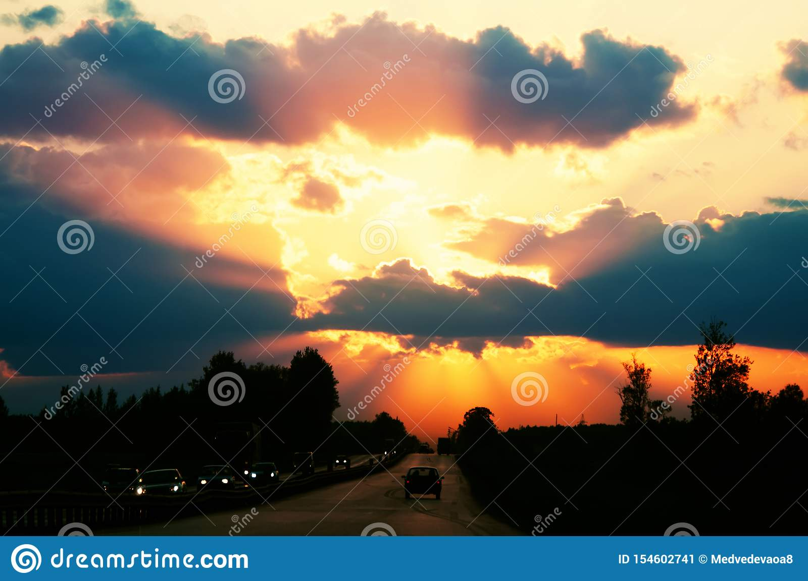 Highway with cars traveling on the sunset. Horizon line with the sun and storm clouds. Journeys. Selective focus
