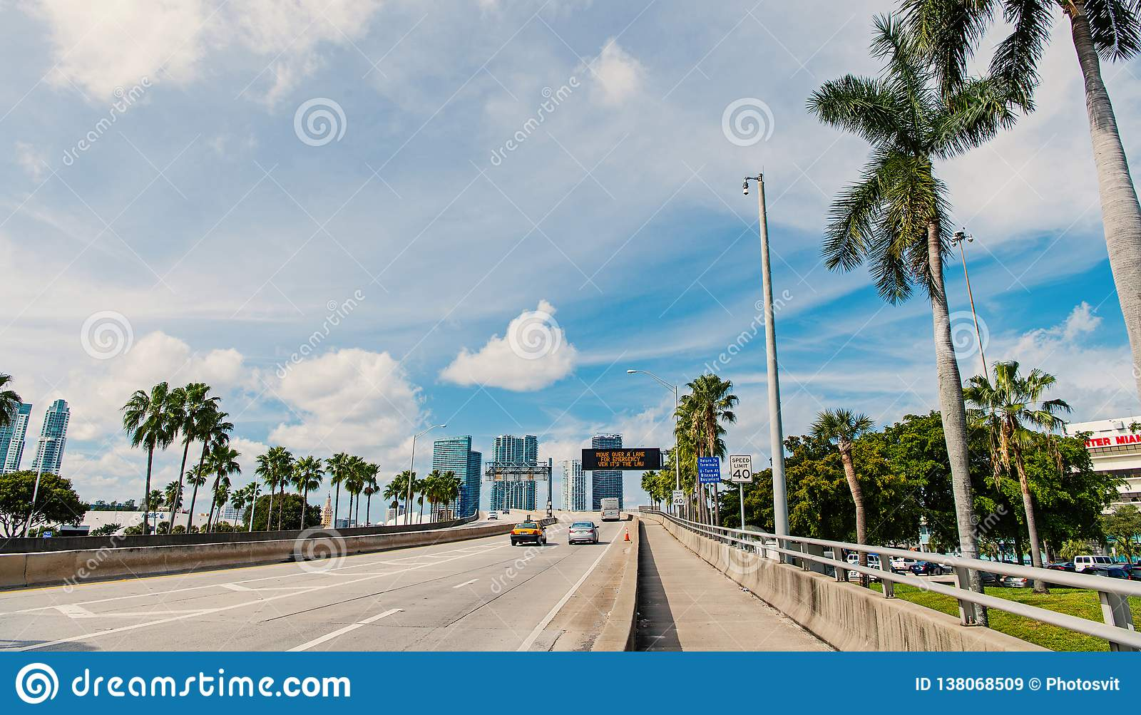 Highway or roadway with cars and skyline of miami, usa. Road with traffic signs for transport vehicles and palm trees on