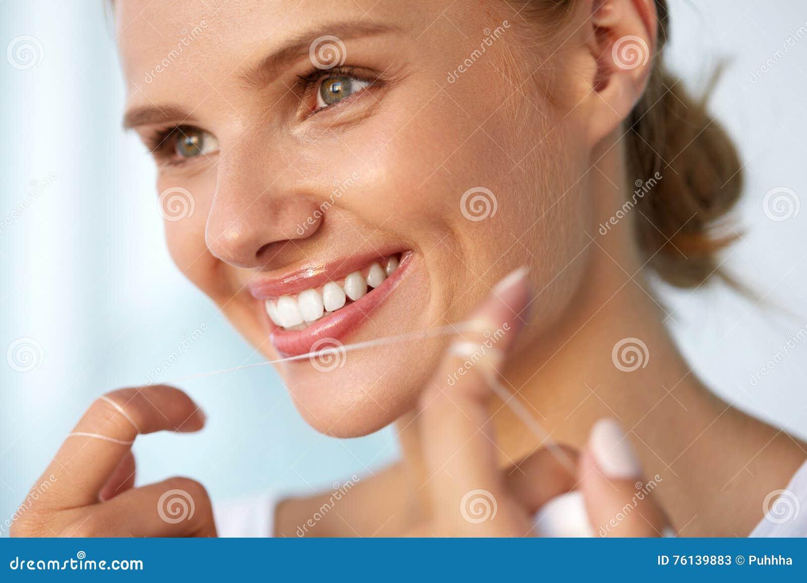 Higiene dental Mulher bonita que Flossing os dentes brancos saudáveis