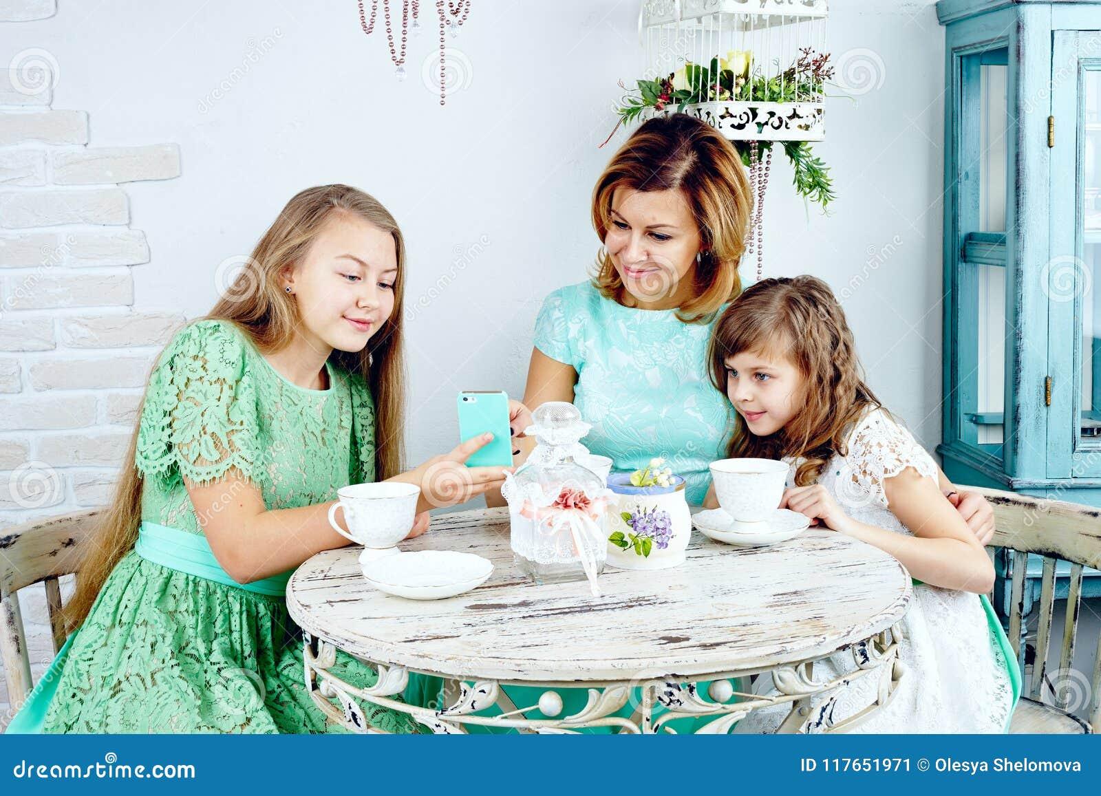 Hija adolescente sonriente que muestra las fotos a la madre y a la hermana