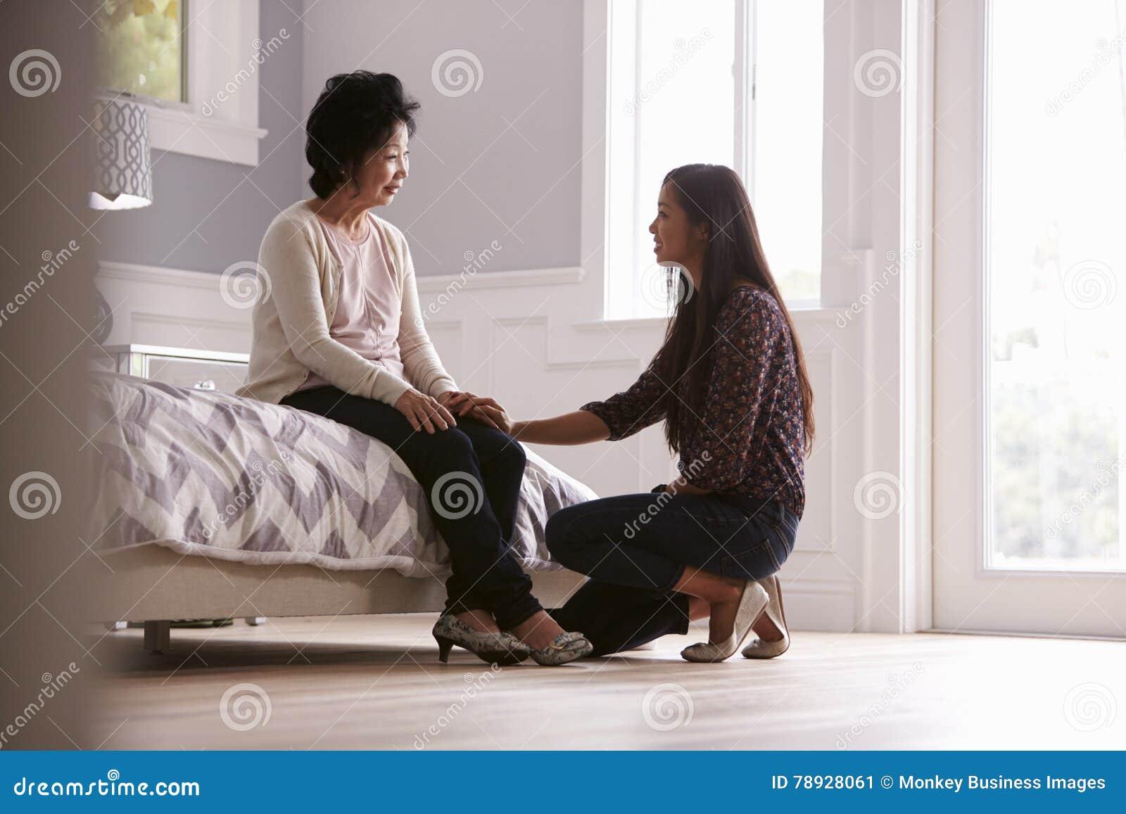 Hija adulta que habla con la madre deprimida en casa