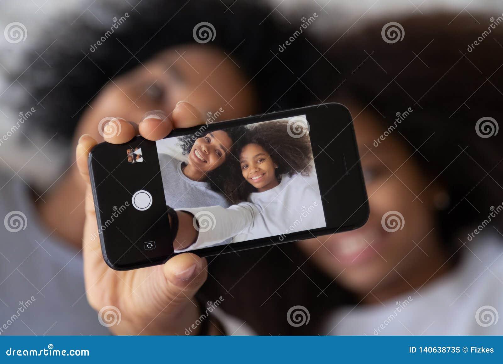 Hija africana de la madre que fotografía mostrando la foto del selfie en smartphone