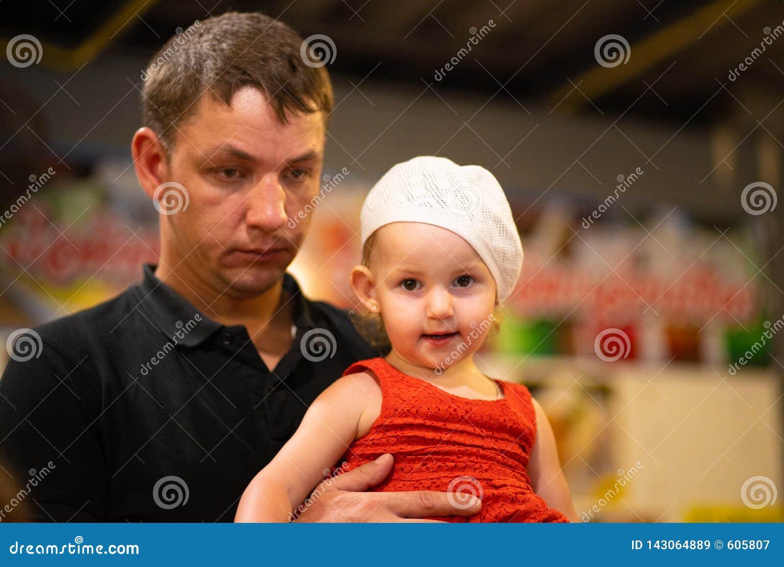Hija cansada en sus brazos, concepto de la tenencia del papá de la paternidad