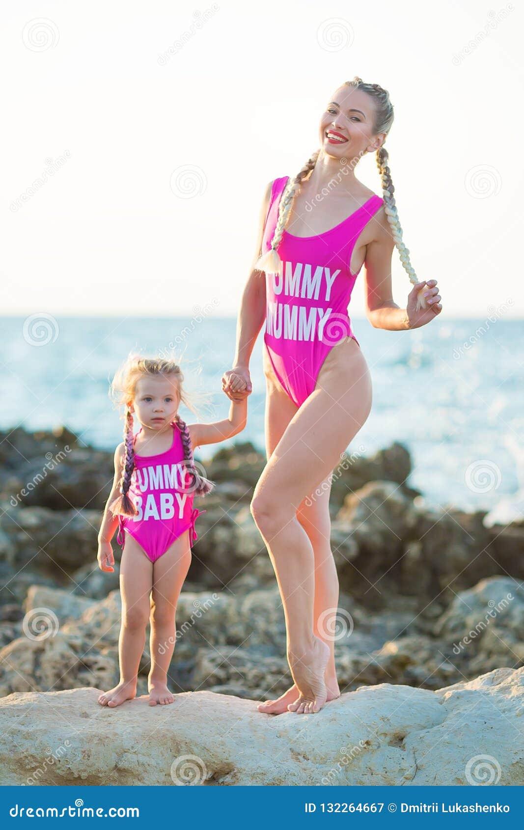 Hija de la madre que se divierte que descansa sobre la playa rocosa que lleva los trajes que nadan rosados La señora rubia con la