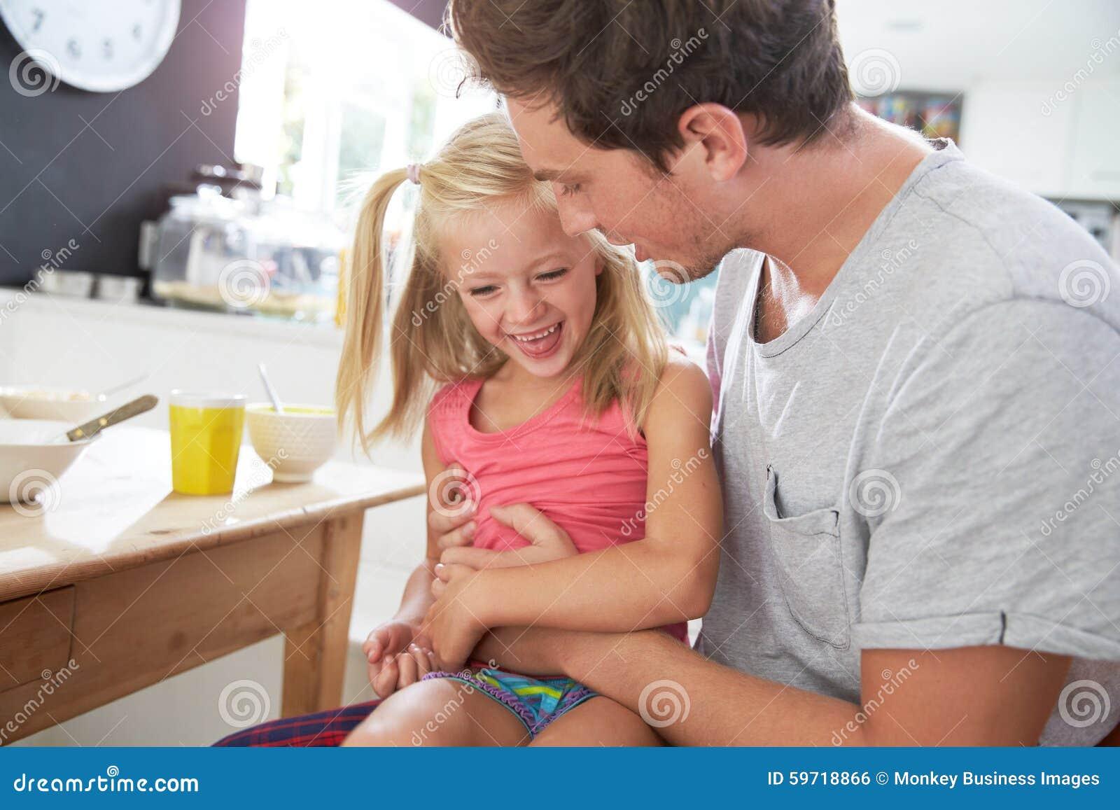 Hija de Sitting With Laughing del padre en la mesa de desayuno