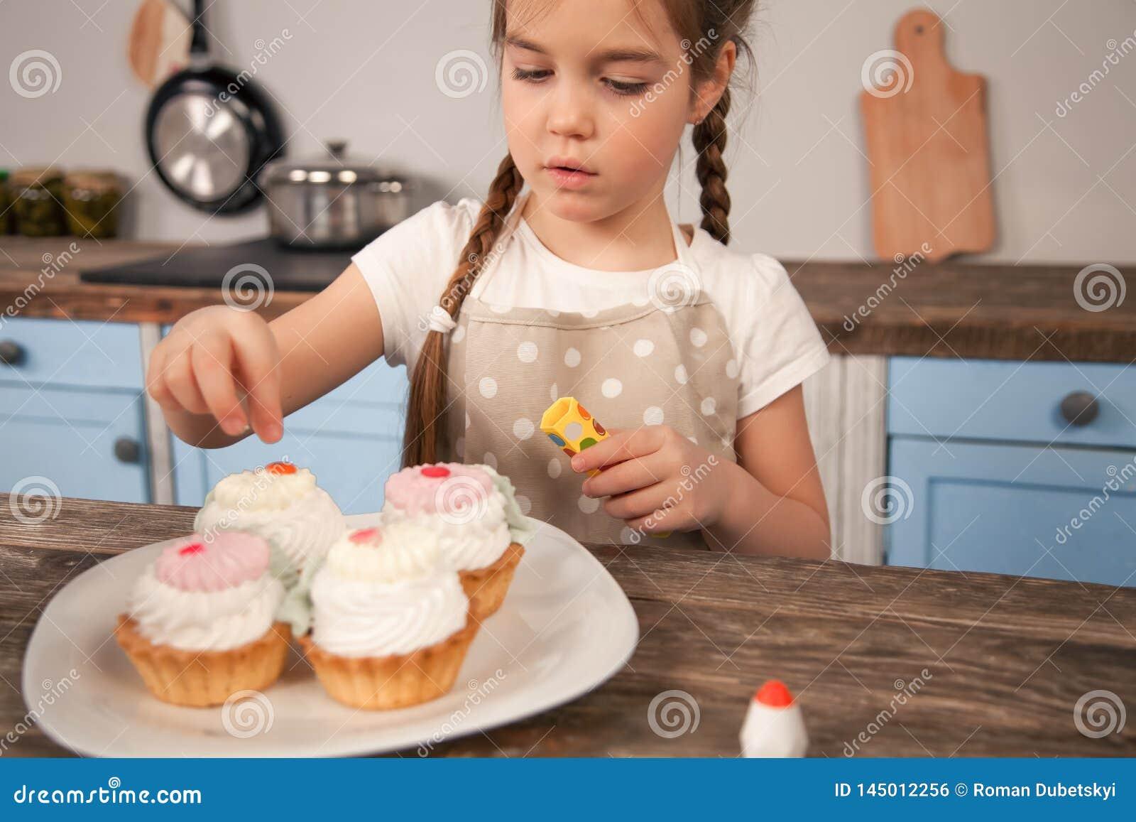 Hija del niño en la cocina que adorna las tortas le hacen con su mamá poco ayudante, comida hecha en casa