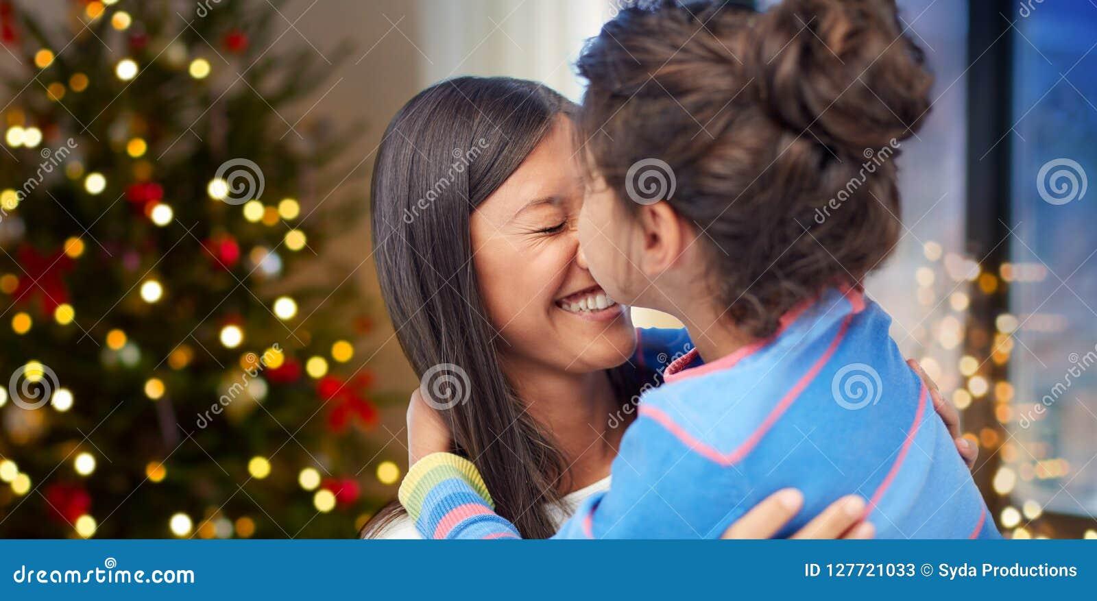 Hija feliz que besa a su madre en la Navidad
