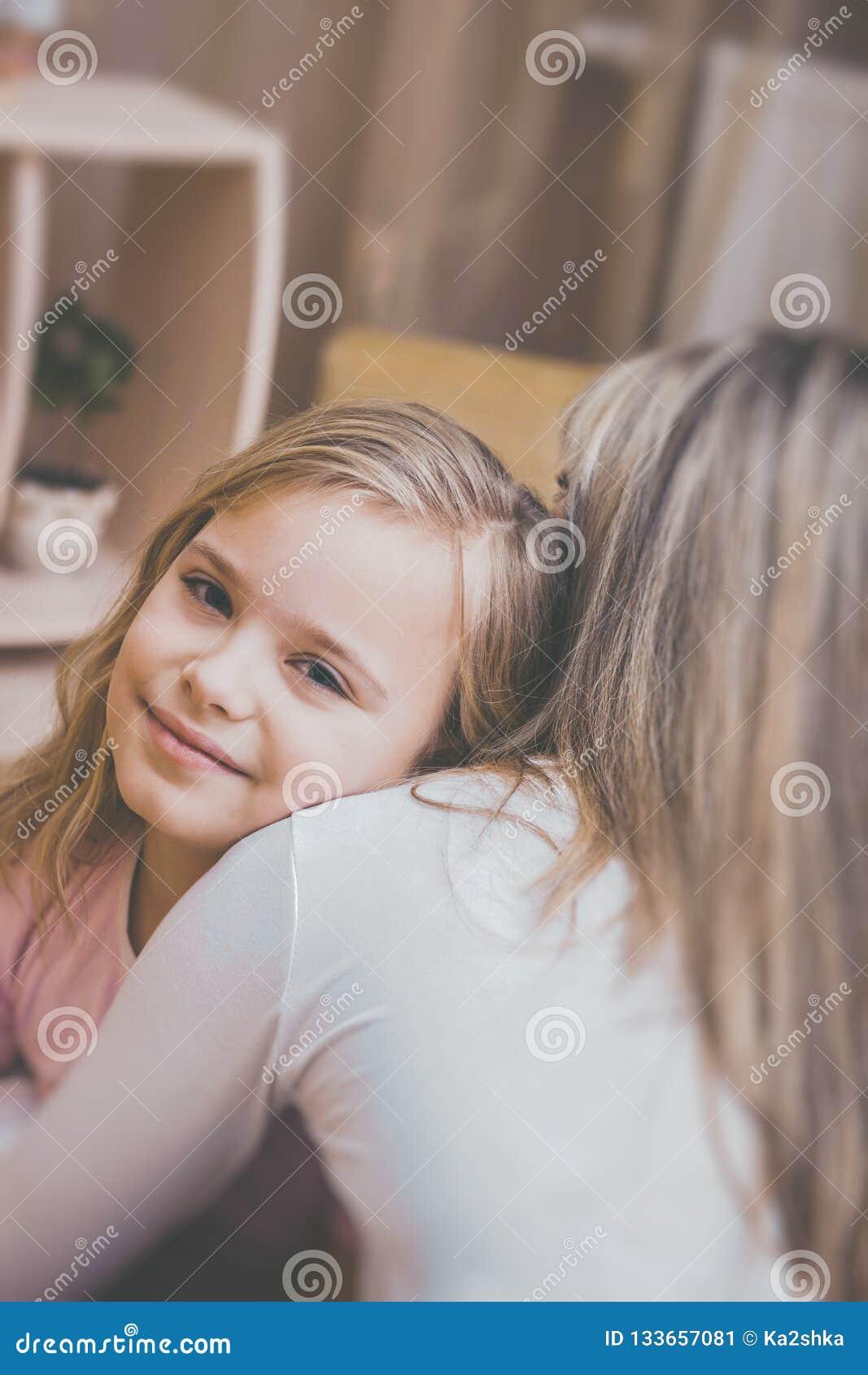 Hija sonriente que abraza a su madre en casa El concepto de familia de los pares está en dolor
