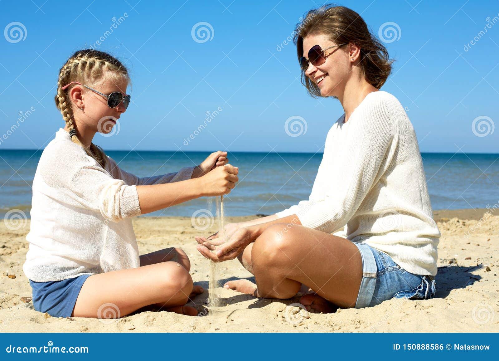 Hija y su mam? que juegan con la arena en la playa
