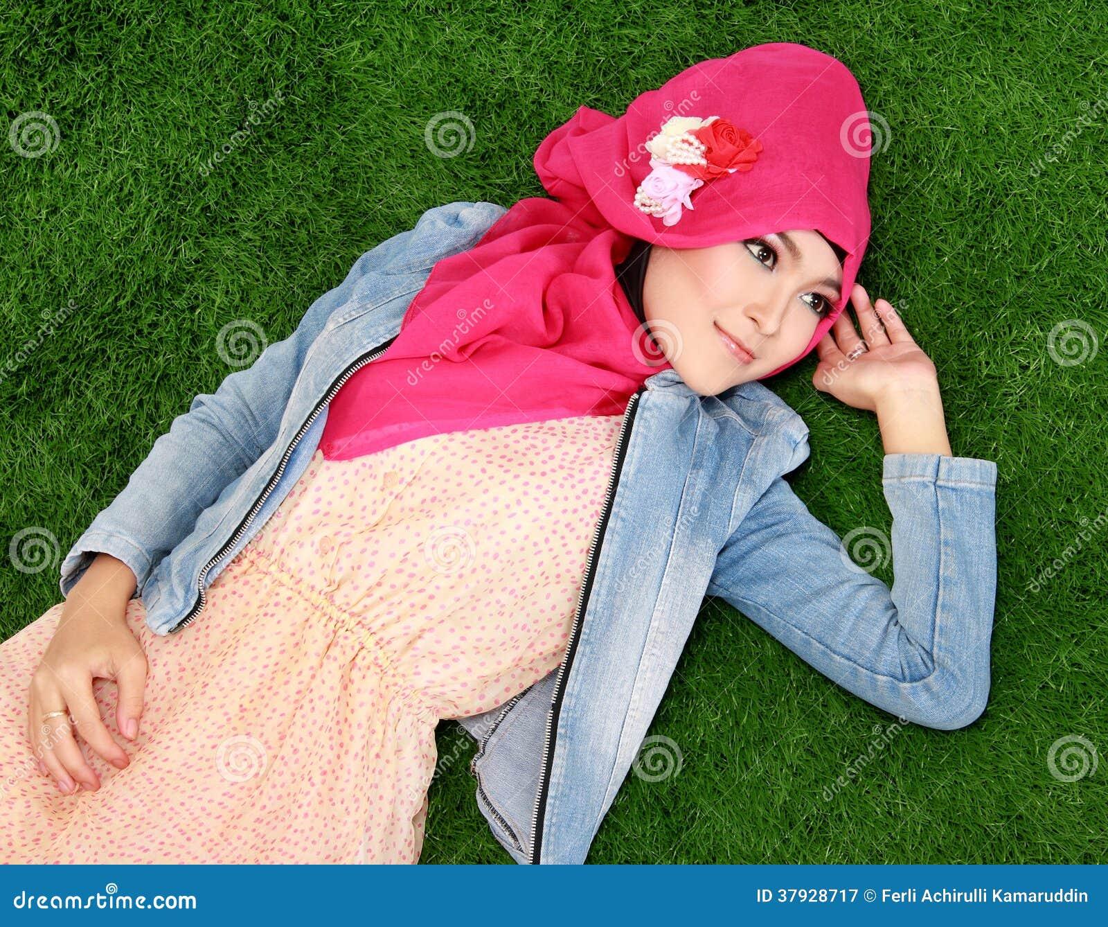 Hijab мусульманской девушки нося лежа на траве
