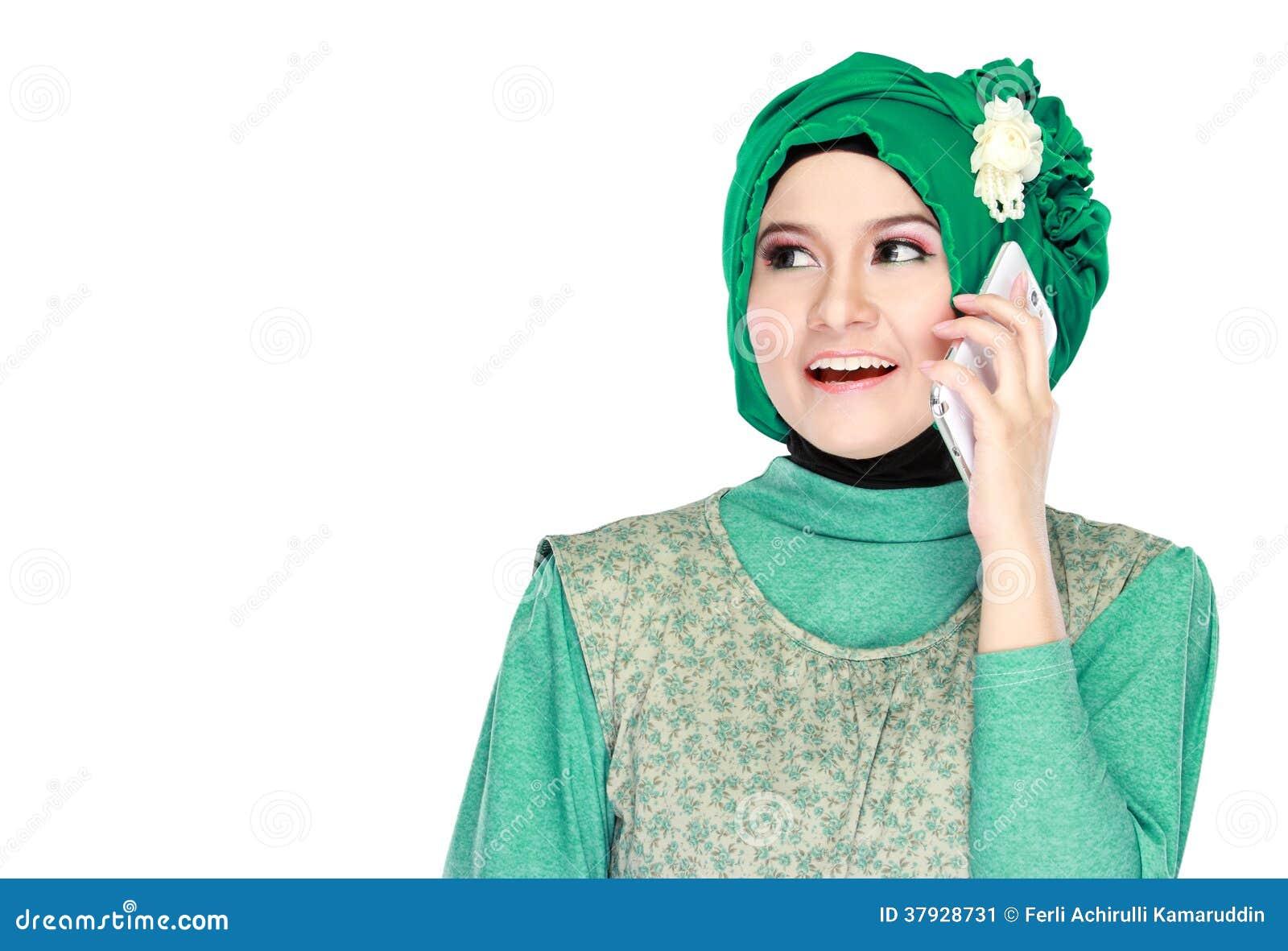 Hijab мусульманской девушки нося сидя на траве