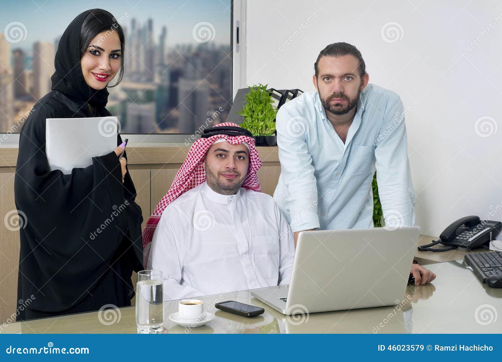 阿拉伯商人&阿拉伯秘书佩带的hijab &一次外国人会议在办公室.图片