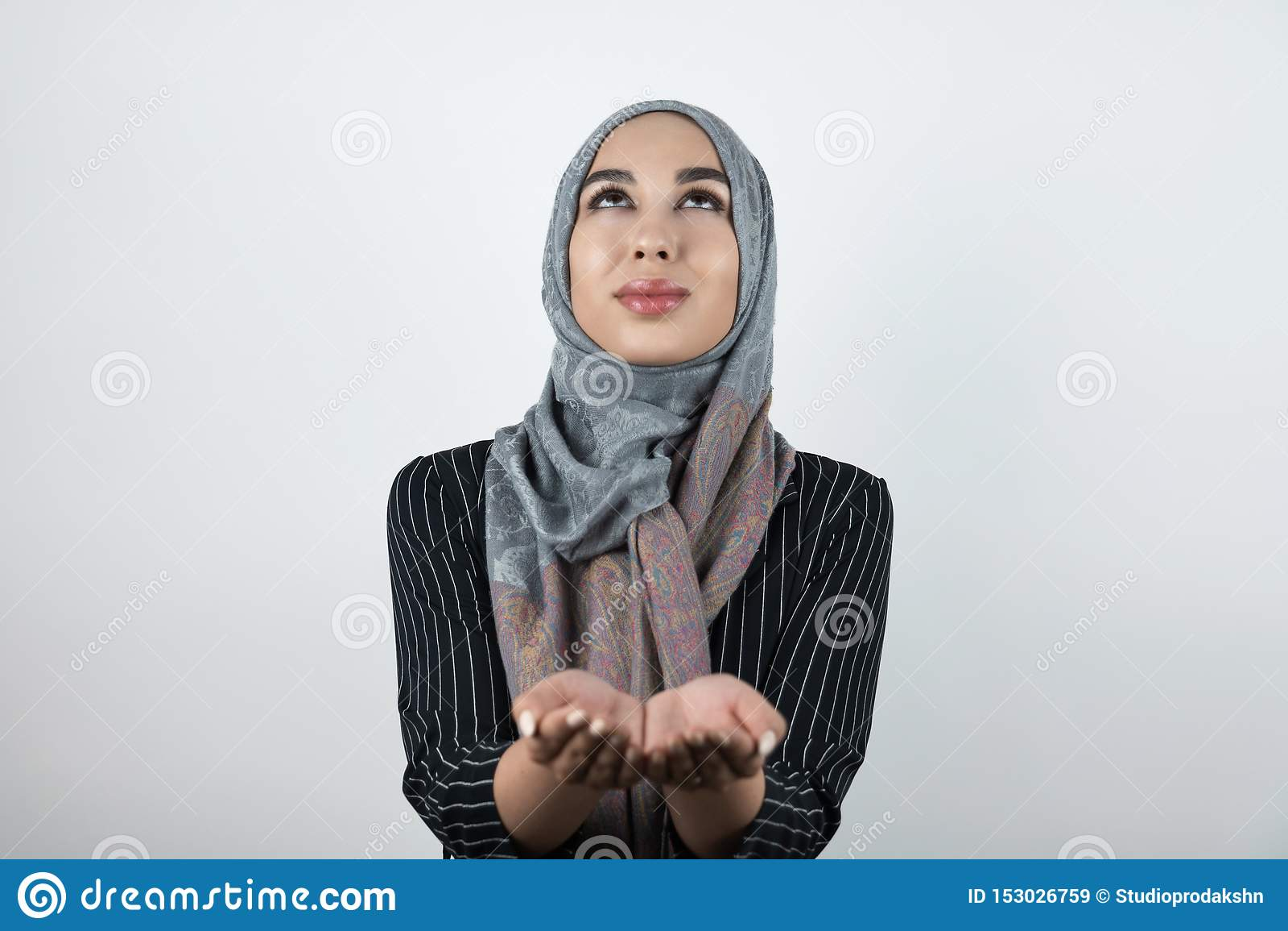 Hijab d uso del turbante della giovane bella donna musulmana promettente, foulard che tiene le sue mani che cercano insieme isola