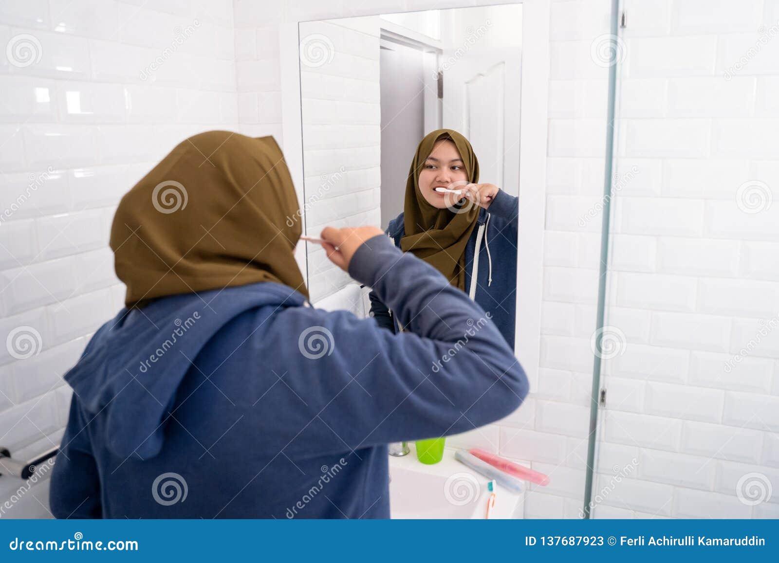 Hijab que lleva de la mujer cepillar sus dientes