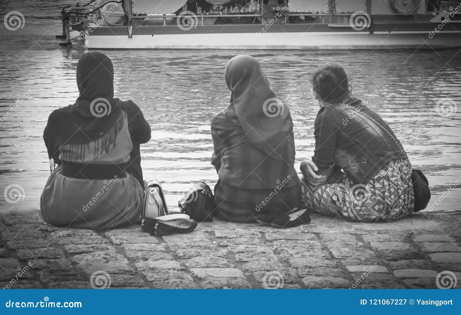 Hijab vestindo da mulher muçulmana que olha no oceano