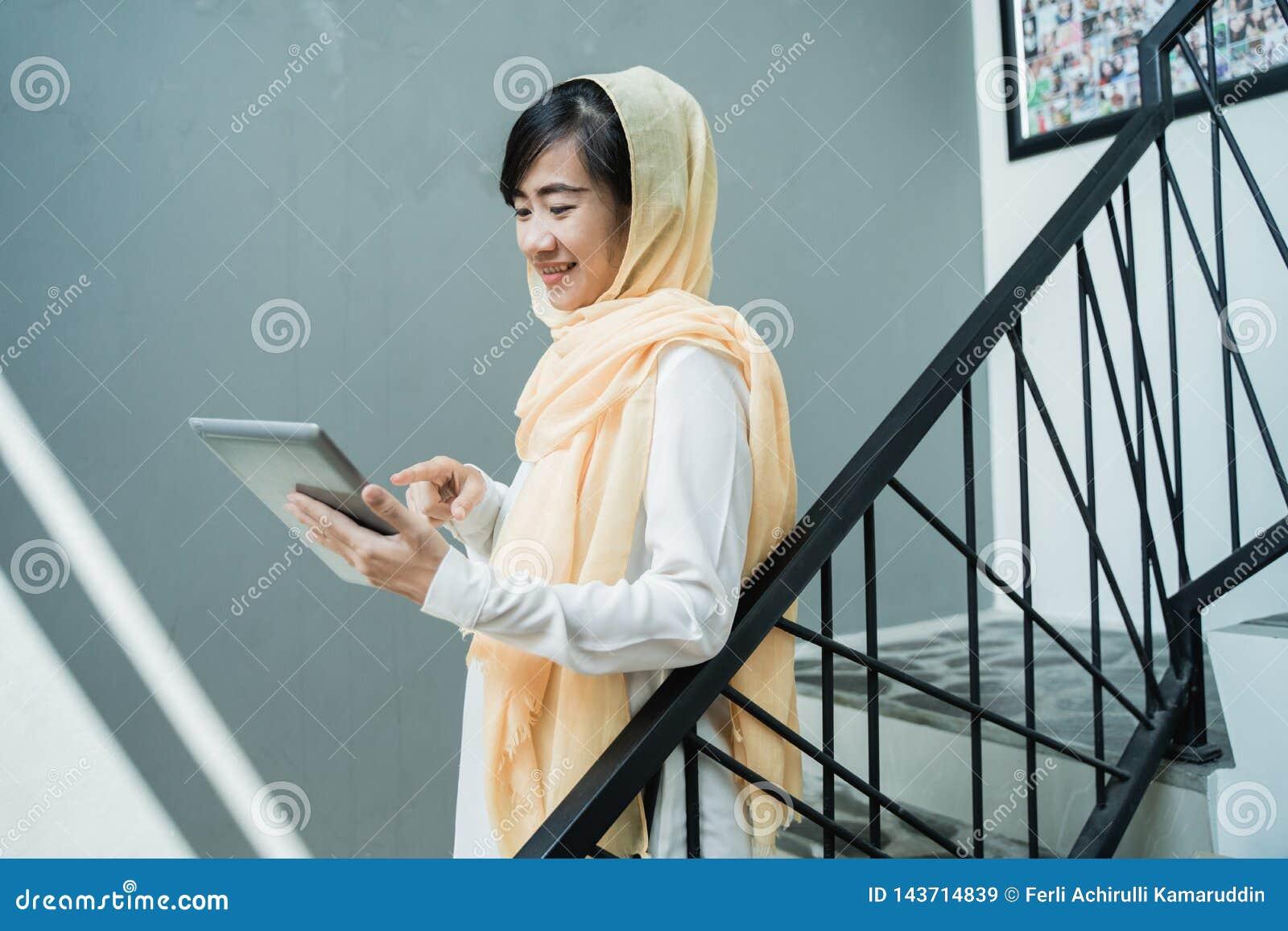 Hijab vestindo da mulher mu?ulmana usando o PC da tabuleta