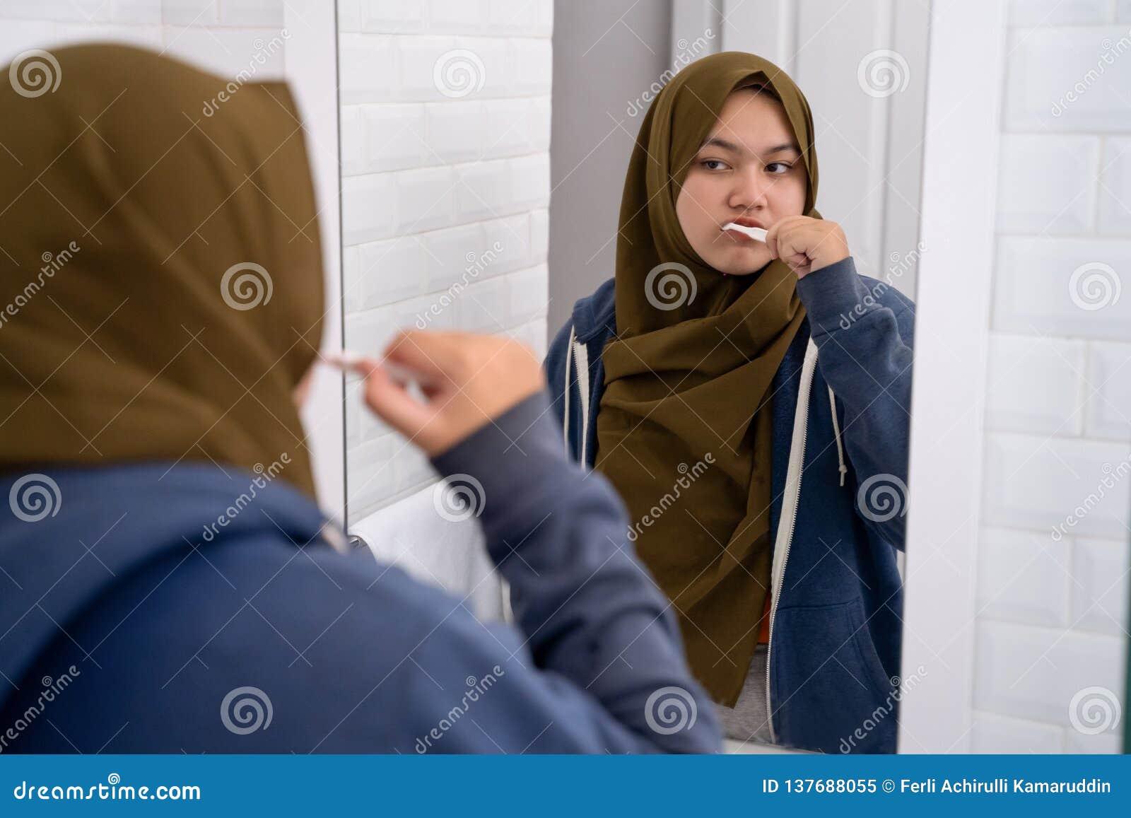 Hijab vestindo da mulher para escovar seus dentes