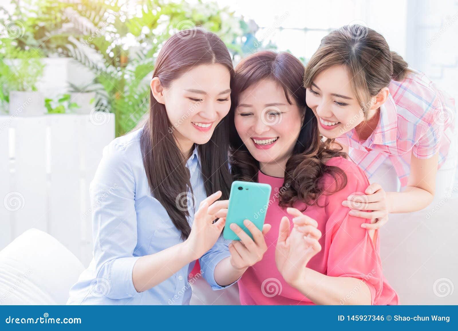 Hijas y smartphone del uso de la madre