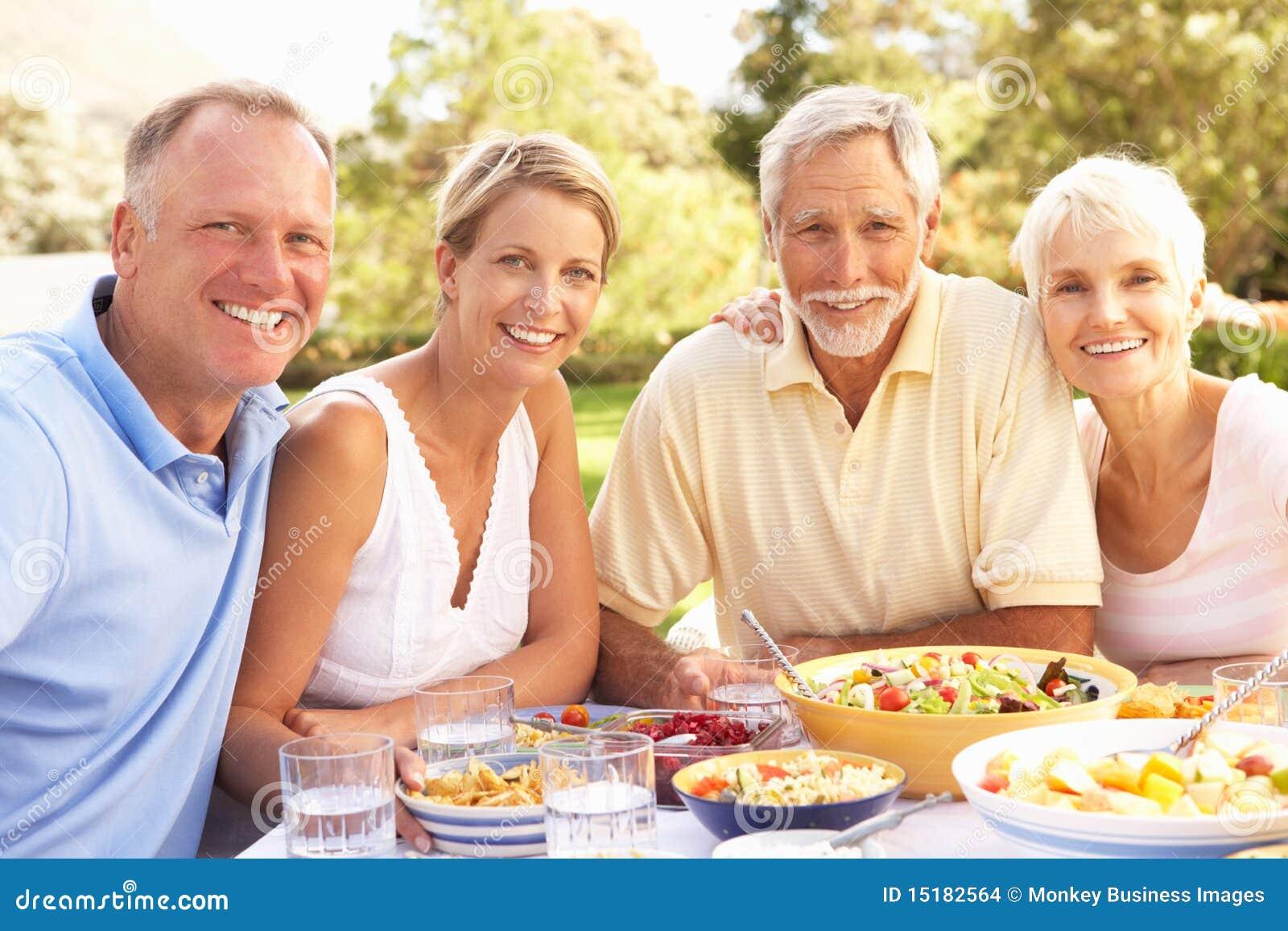 Hijo adulto e hija que disfrutan de la comida en jardín