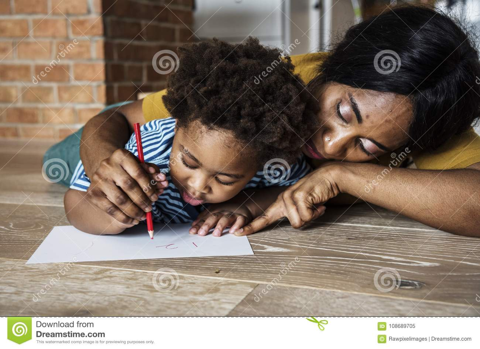 Hijo de enseñanza de la mamá cómo al dibujo