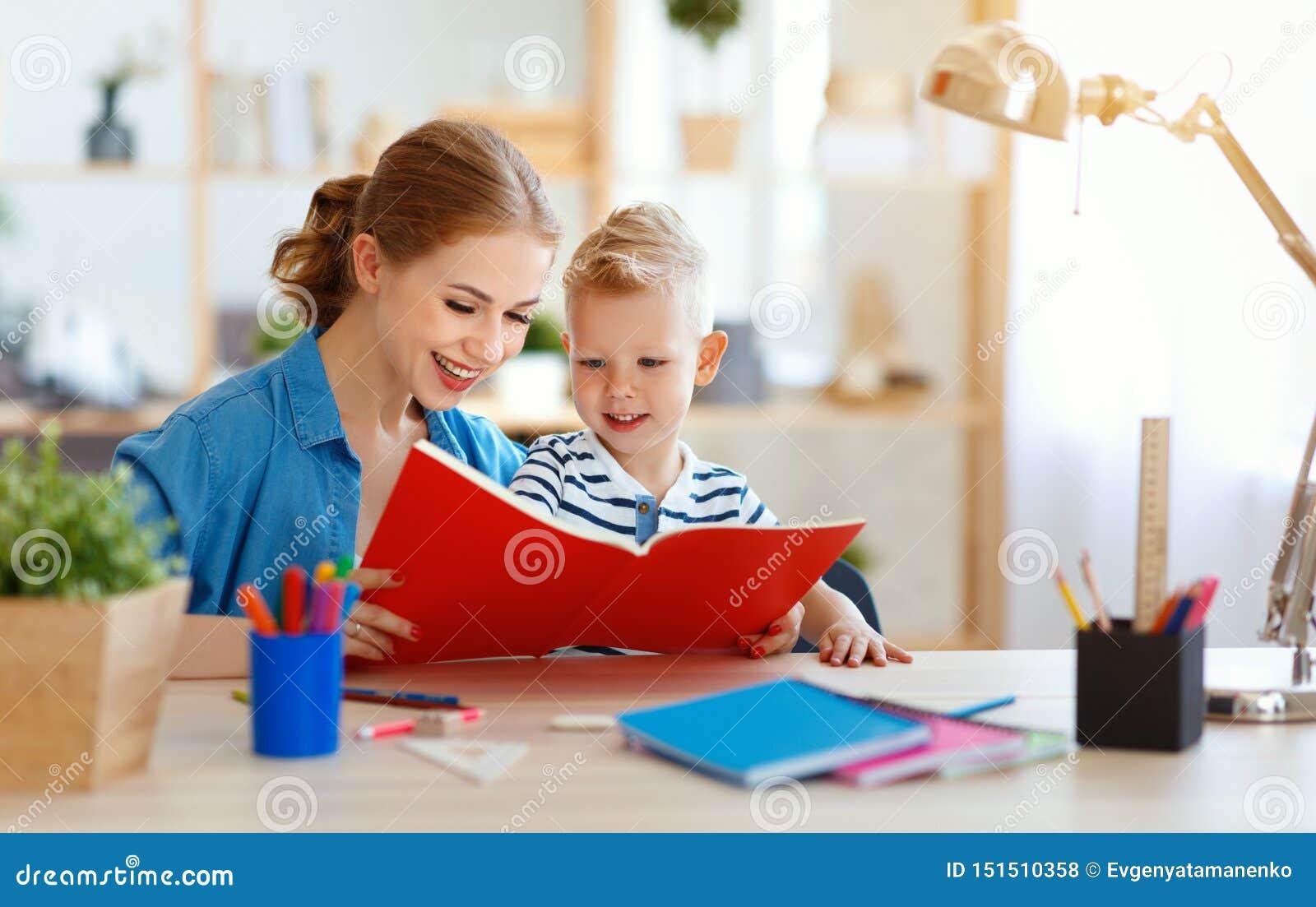 Hijo de la madre y del niño que hace la escritura de la preparación y que lee en casa