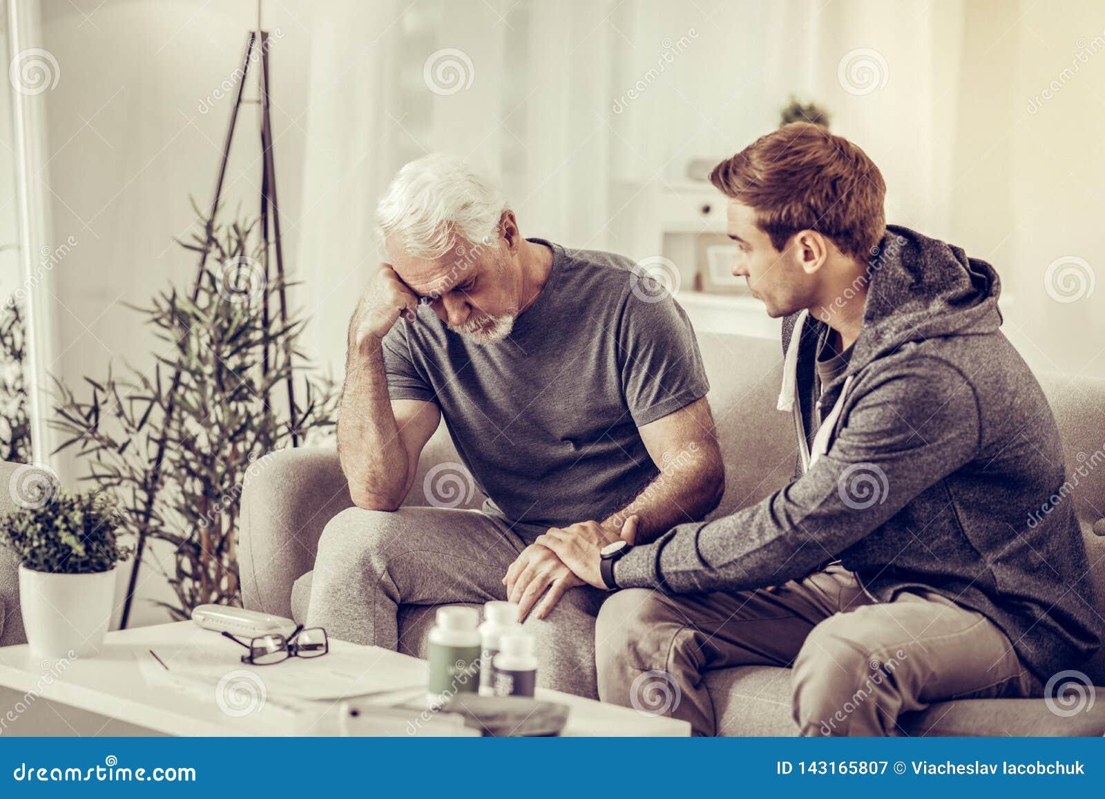 Hijo de pelo corto del Joven-adulto que conforta al padre trastornado gris-cabelludo mayor en la sala de estar