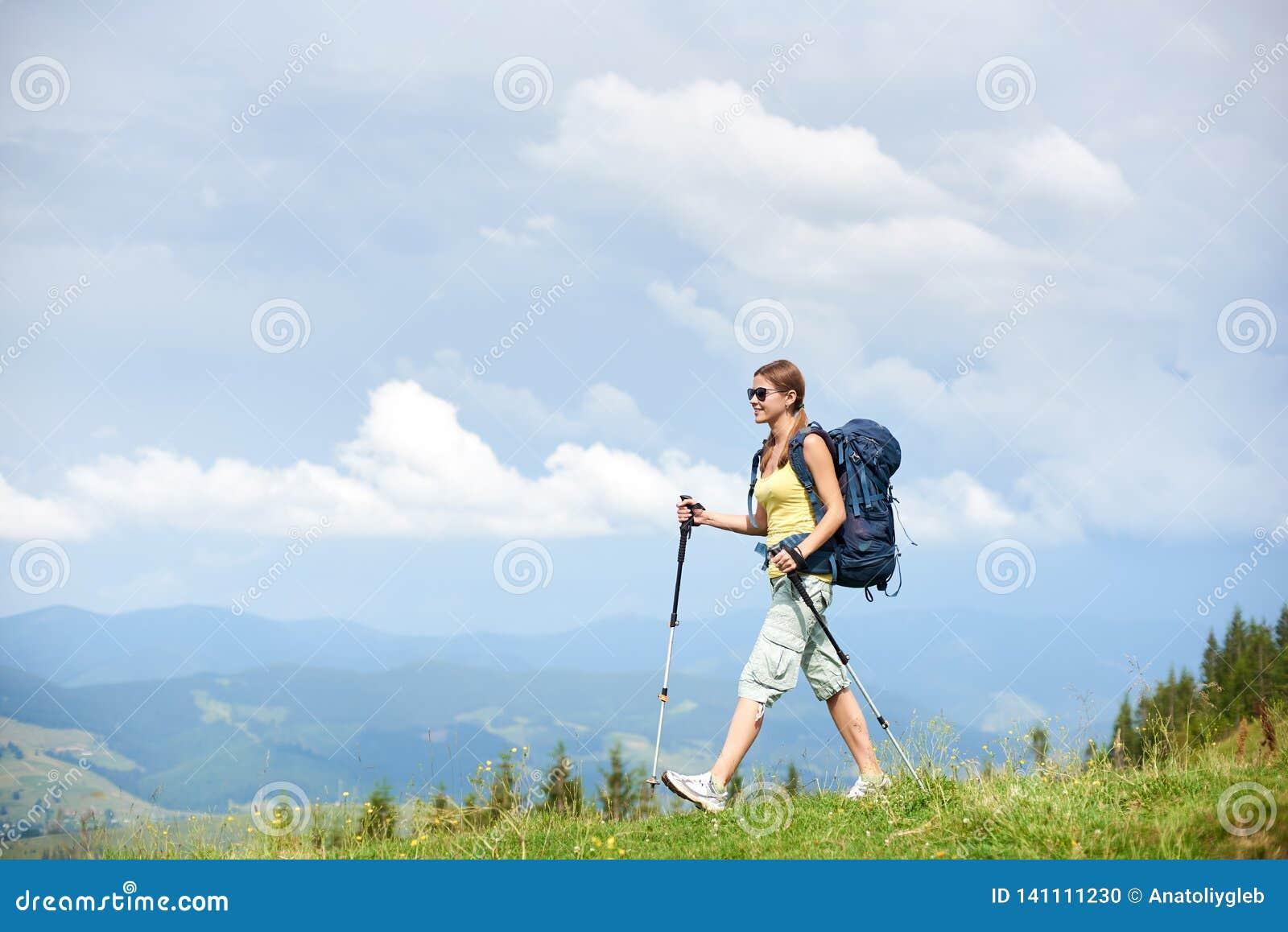 Hiker женщины на травянистом холме, нося рюкзаке, используя trekking ручки в горах