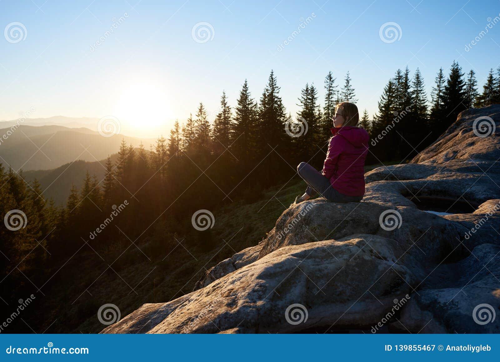 Hiker женщины сидя на валуне в горах на заходе солнца