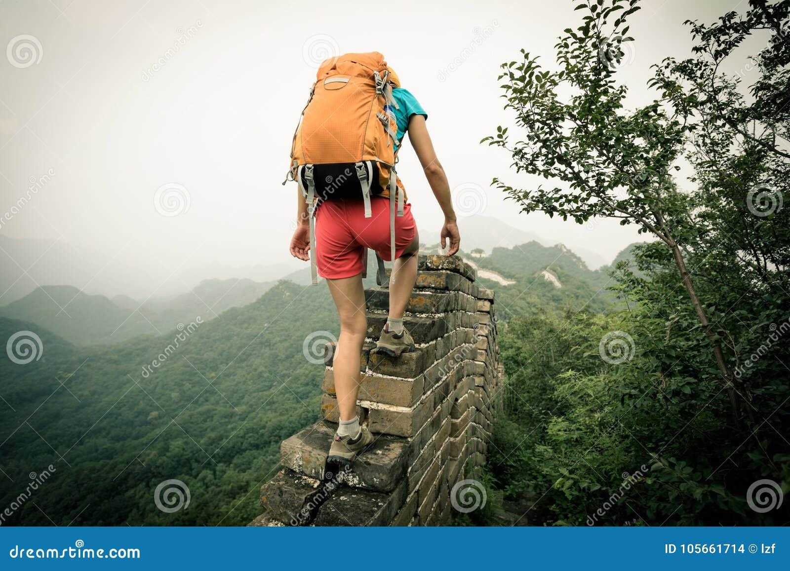 Hiker женщины взбираясь вверх на верхней части Великой Китайской Стены