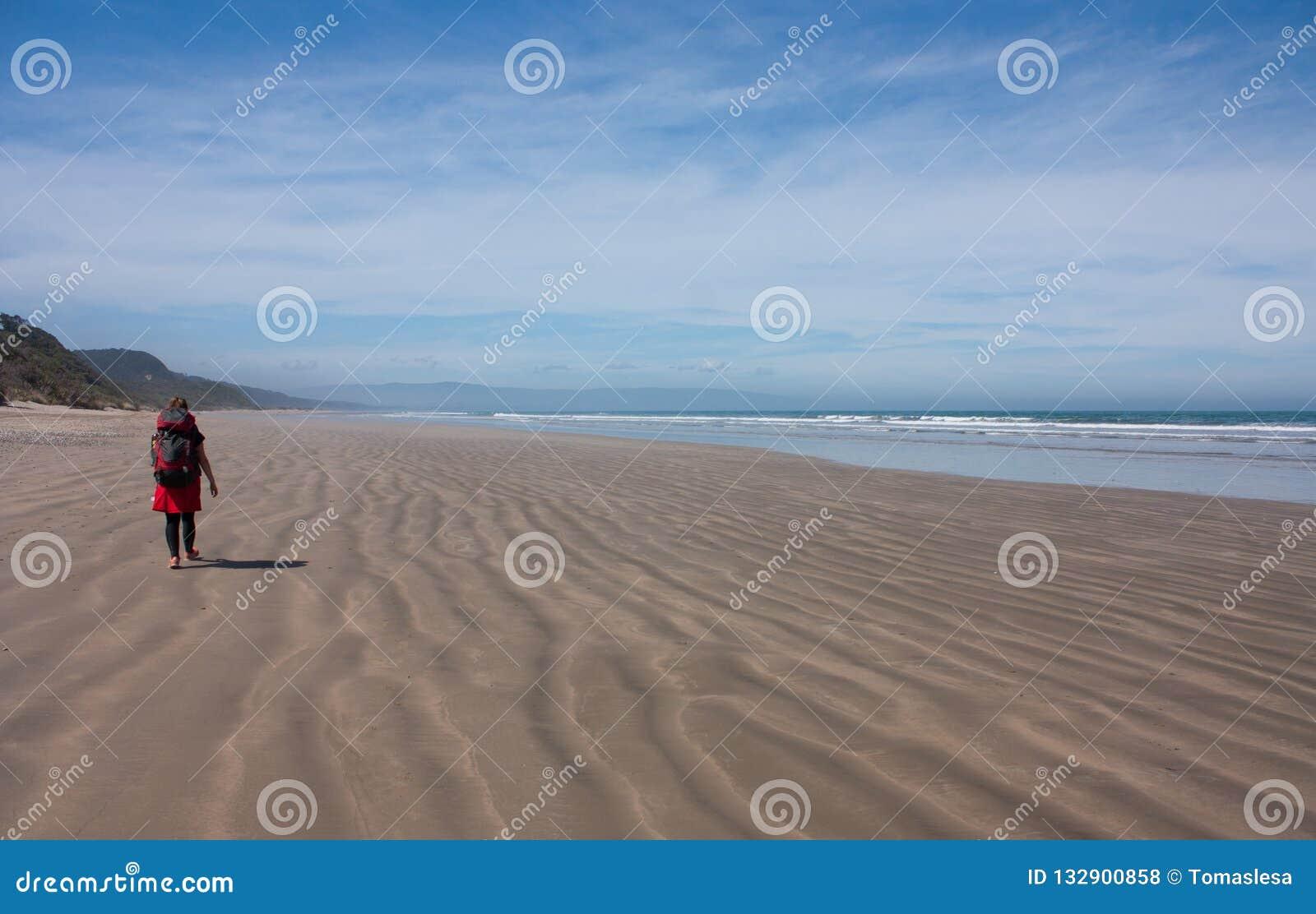 Hiker женщины идя на пляж с ее рюкзаком на следе Humpridge в Fiordland/Southland в южном острове в новом