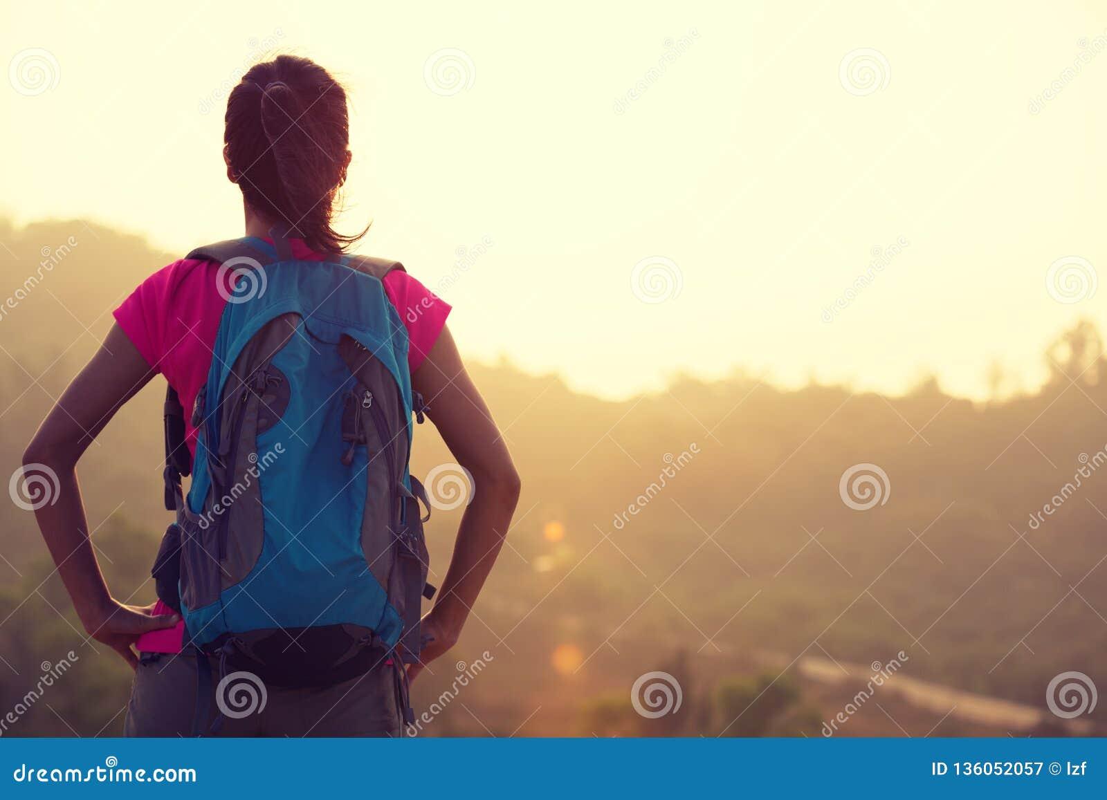 Hiker женщины наслаждается взглядом на восходе солнца