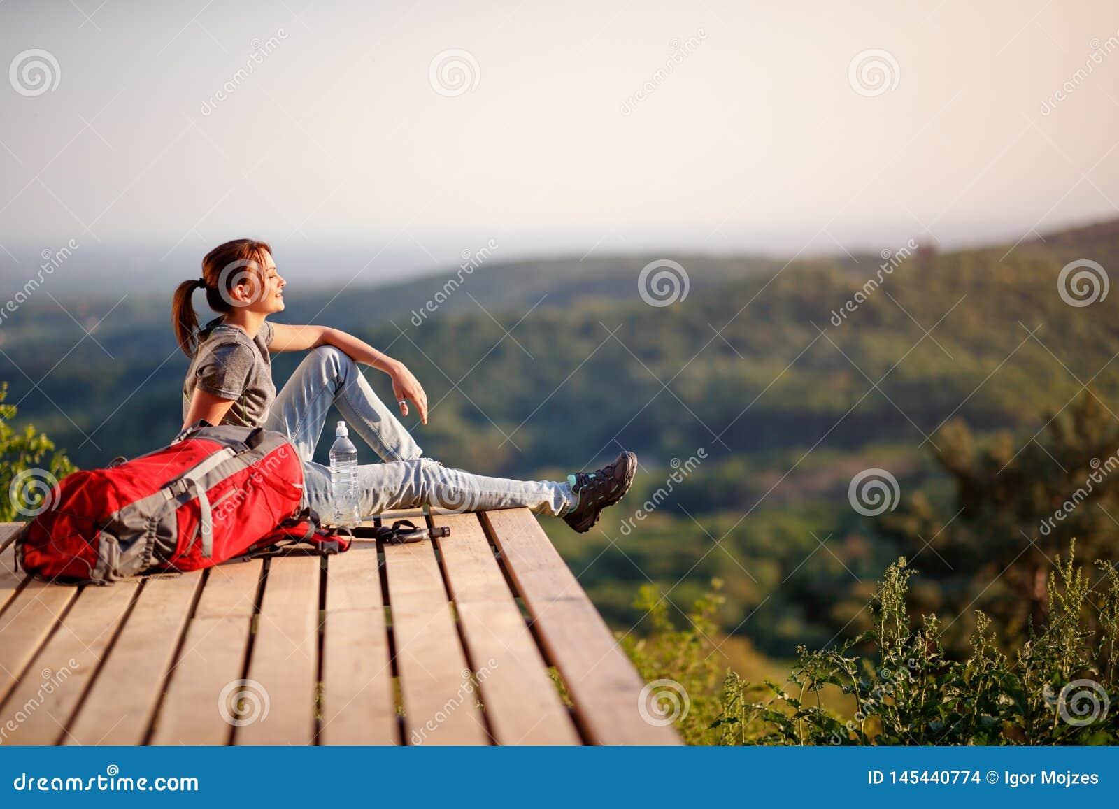 Hiker наслаждаясь на солнце на перерыве от пешего туризма