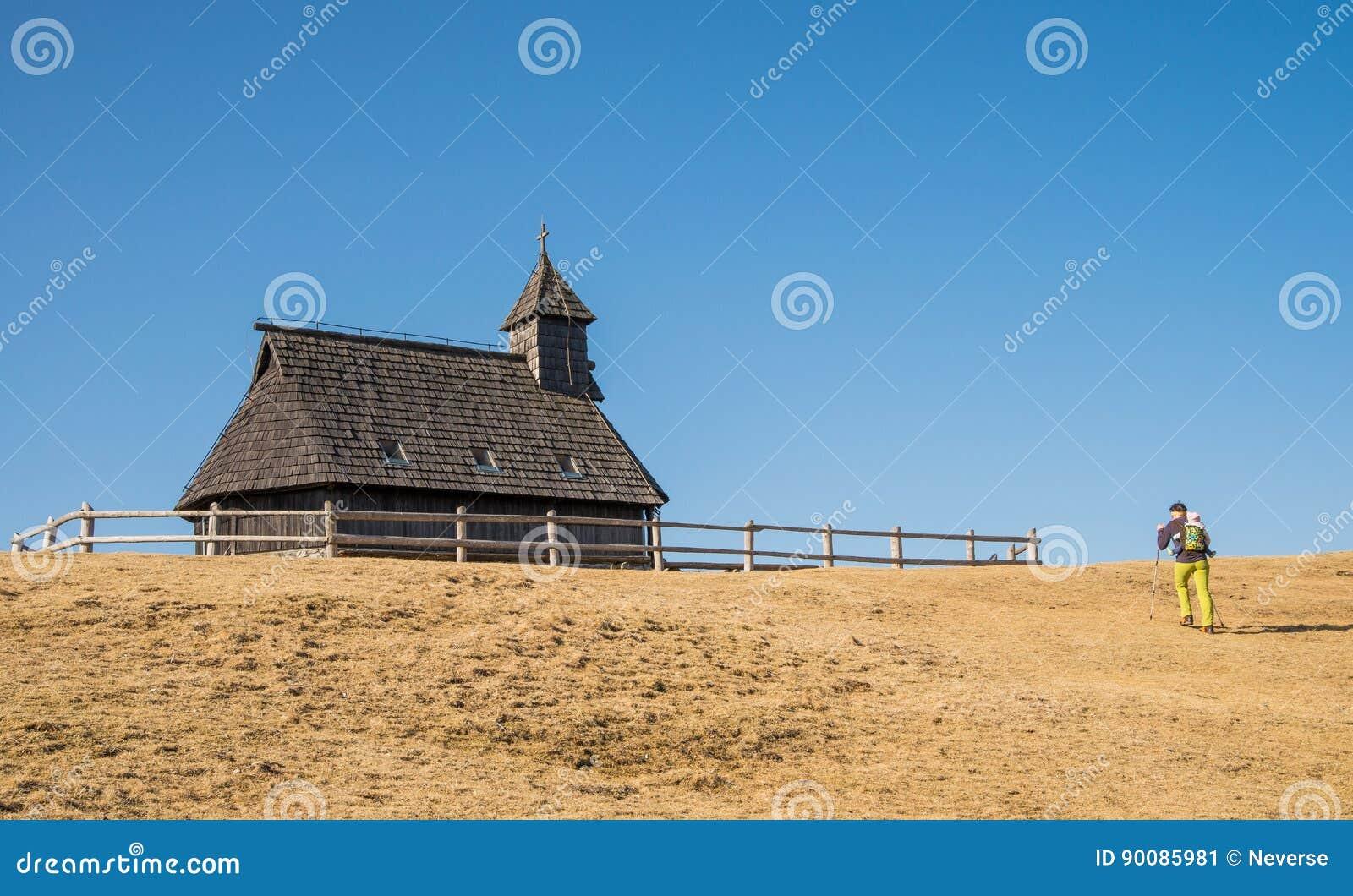 Hiker около церков raditional деревянной на Velika Planina