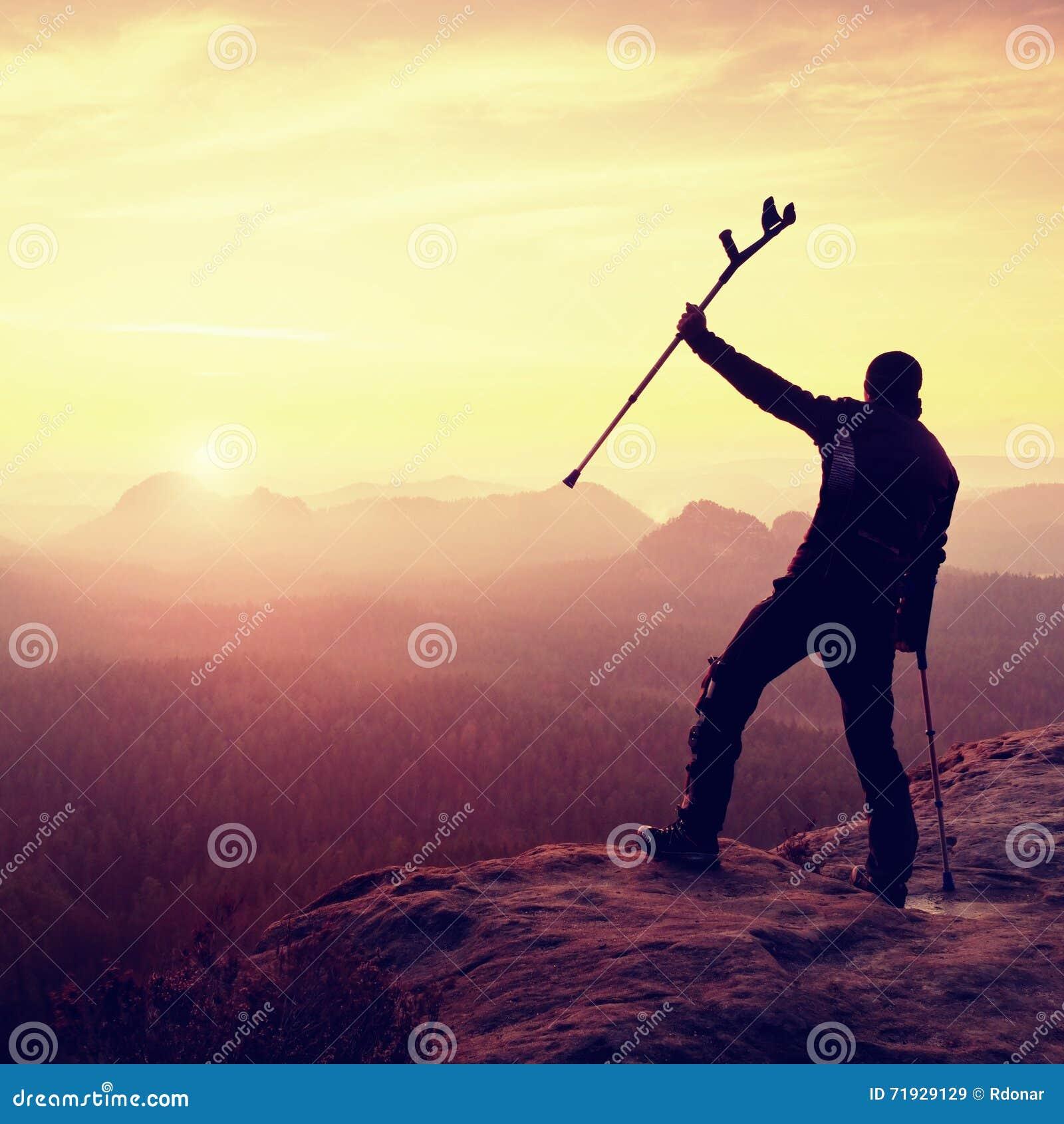 Hiker с костылем медицины над головой достиг горного пика