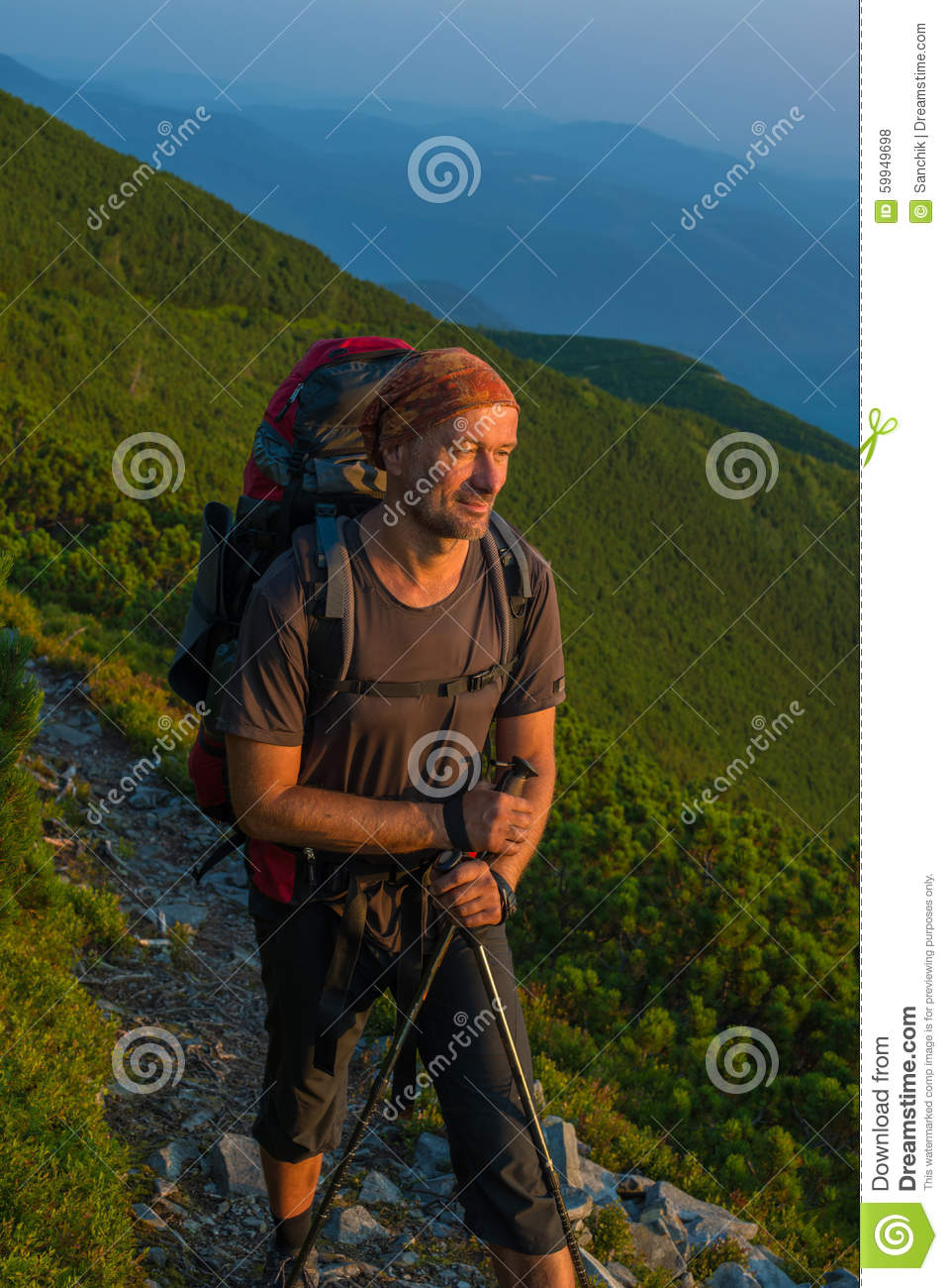 Hiker with backpack is resting and looks at the rising sun in mo