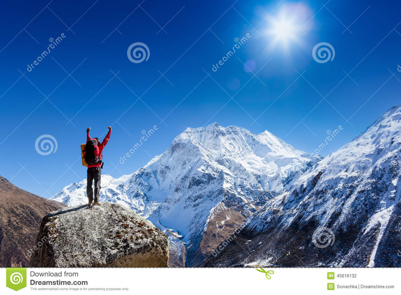Hiker cheering elated and blissful with arms raised in the sky after hiking to mountain top summit