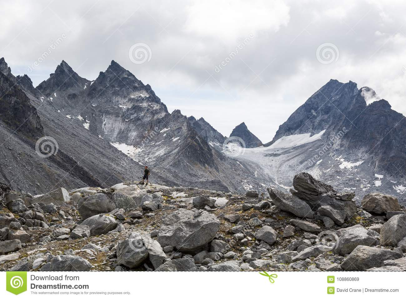 Man Standing Below Huge Cirque Glacier And Rocky Peaks In The